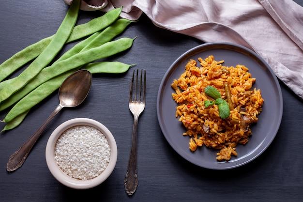 Paella des gemüses und des huhns auf schwarzer tabelle, schüssel reis, bohnen und löffel und gabel Premium Fotos
