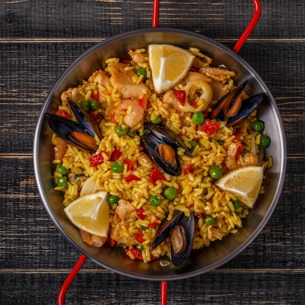 Paella mit hühnchen, meeresfrüchten, gemüse und safran in der traditionellen pfanne. Premium Fotos