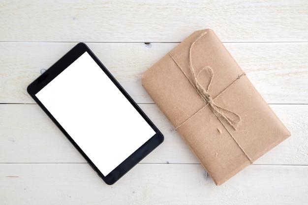 Paket, geschenk verpackt im umweltfreundlichen papier und in der tablette auf hellem hölzernem hintergrund. der blick von oben Premium Fotos
