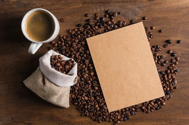 Paket in der nähe von tasse und sack mit kaffeebohnen Kostenlose Fotos