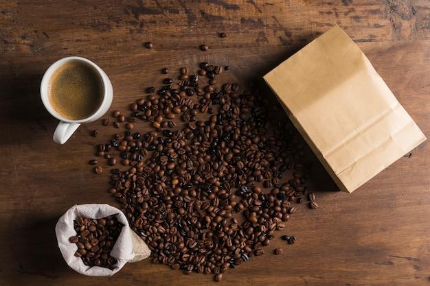 Paket, sack und tasse in der nähe von kaffeebohnen Kostenlose Fotos