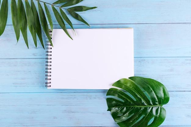 Palmblätter und ein papiernotizbuch mit freiem platz für text auf blauem hölzernem hintergrund. Premium Fotos