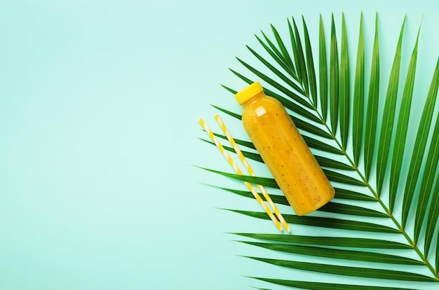 Palmblätter und eine flasche orange, ananas, mango smoothie, stroh auf blauem hintergrund. detox sommergetränk. vegetarisches konzept. Premium Fotos