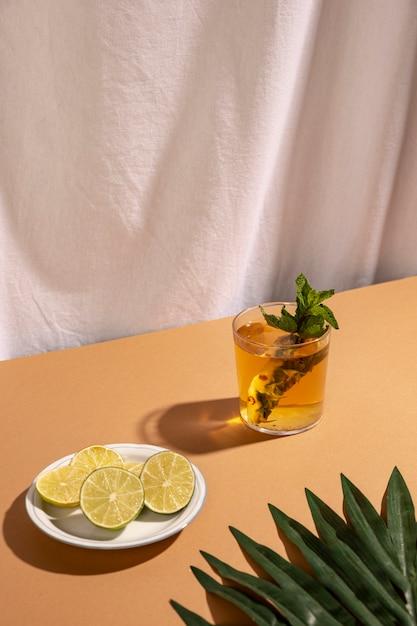 Palmblatt mit zitronenscheiben und cocktailgetränk über brauner tabelle Kostenlose Fotos