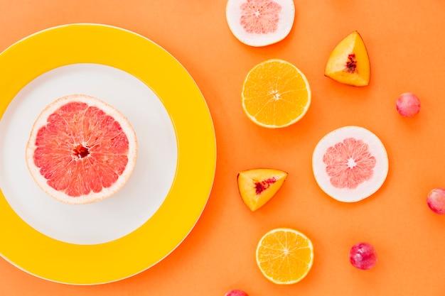 Pampelmusenscheibe auf weißer und gelber platte mit früchten auf einem orange hintergrund Kostenlose Fotos