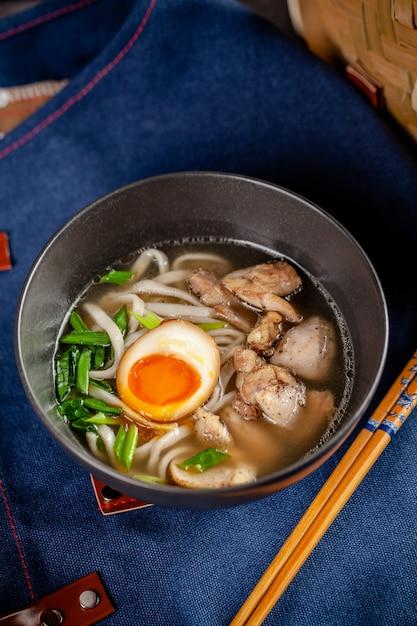 Panasiatische küche-konzept. japanische ramen-suppe mit chinesischen nudeln, ei, huhn und frühlingszwiebeln. servierteller im restaurant in der schüssel. hintergrundbild. kopieren sie platz Premium Fotos