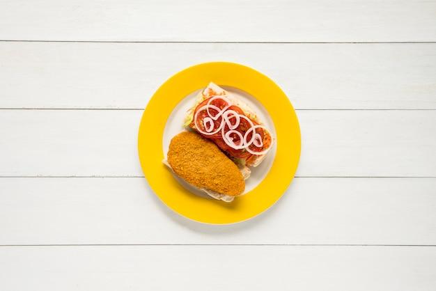 Panierte hühnerbrust und frischgemüsesandwich auf holztisch Kostenlose Fotos