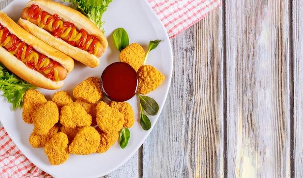 Panierte hühnernuggets und hot dog mit senf auf weißem teller. Premium Fotos