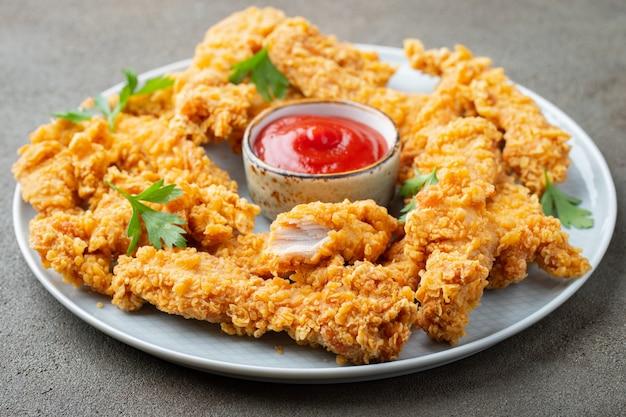 Panierte hühnerstreifen mit saucen. Premium Fotos