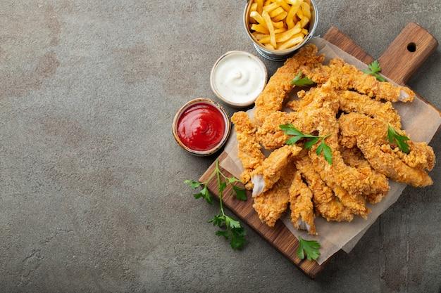Panierte hühnerstreifen mit zwei saucen. Premium Fotos