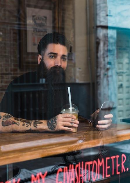 Paniertes sitzendes café des mannes mit handy und kaffee in der hand Kostenlose Fotos