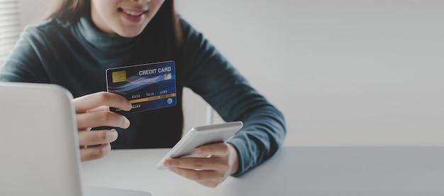 Panorama-banner. junge frau sicherheitscode mit handy smartphone eingeben und bezahlen kreditkarte am schreibtisch zu hause büro Premium Fotos