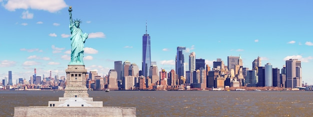 Panorama des freiheitsstatuen mit dem one world trade building center über dem hudson river und dem new york cityscape-hintergrund, marksteine von unterem manhattan new york city. Premium Fotos