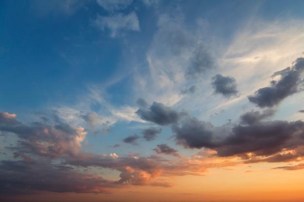 Panorama des himmels bei sonnenaufgang oder sonnenuntergang. schöne ansicht von dunkelblauen wolken beleuchtete durch helle sonne des orange gelbs auf klarem himmel. schönheit und kraft der natur, meteorologie und klimakonzept. Premium Fotos
