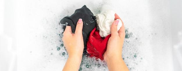 Panorama von den weiblichen händen, die schwarze, rote und weiße kleidung im weißen schaum waschen Premium Fotos