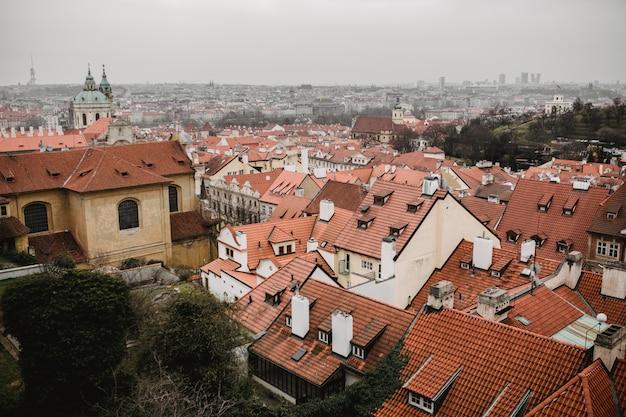 Panorama von prag mit roten dächern und kirche. stadtansicht der altstadt von praha. rustikale graue farbtöne Premium Fotos
