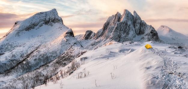 Panorama von steilen höchstbergen mit bedecktem schnee und gelbem zelt Premium Fotos