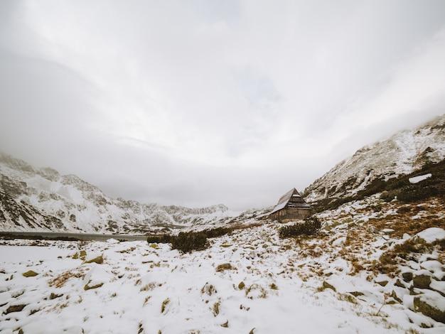 Panoramaaufnahme einer winterlandschaft mit einer kleinen hütte am tatragebirge in polen Kostenlose Fotos