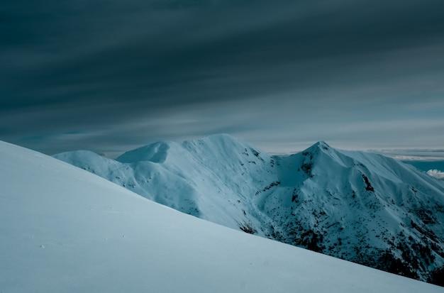 Panoramaaufnahme von schneebedeckten berggipfeln unter bewölktem himmel Kostenlose Fotos