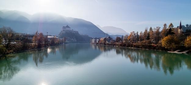 Panoramablick auf die glatte oberfläche des flusses vor der festung kufstein, österreich. Premium Fotos