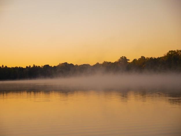 Panoramablick auf nebel, der während der dämmerung auf der wasseroberfläche sitzt Kostenlose Fotos