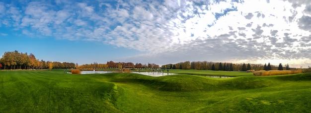 Panoramablick auf teich und grüne wiese im herbstpark. oktober wald und see, naturlandschaft am sonnigen tag Premium Fotos