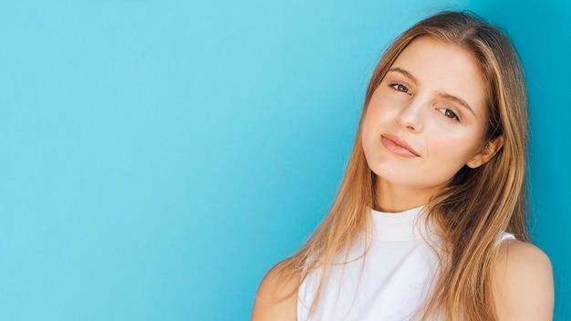 Panoramablick der blonden jungen frau gegen blauen hintergrund Kostenlose Fotos