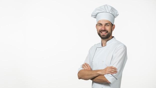 Panoramablick des glücklichen männlichen chefs mit seinem arm kreuzte gegen weißen hintergrund Premium Fotos