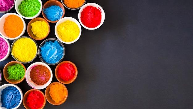 Panoramablick des holi farbpulvers in den schüsseln auf schwarzem hintergrund Kostenlose Fotos