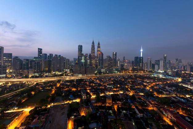 Panoramablick von kuala lumpur-stadtskylinen während der sonnenaufgangbetrachtungswolkenkratzer, die in malaysia errichten. Premium Fotos