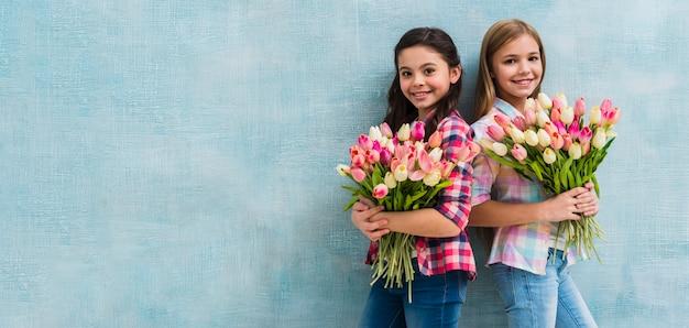 Panoramablick von lächelnd zwei mädchen, die rosa und gelben tulpenblumenstrauß in den händen halten Kostenlose Fotos