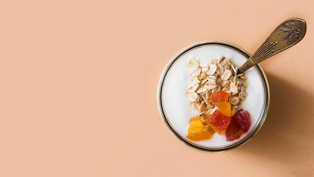 Panoramablick von sauerrahmjoghurt mit den hafern und früchten, die im glas übersteigen Kostenlose Fotos
