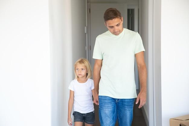 Papa führt eine hübsche blondhaarige tochter in ihre neue wohnung, hält die hand und geht in den korridor Kostenlose Fotos