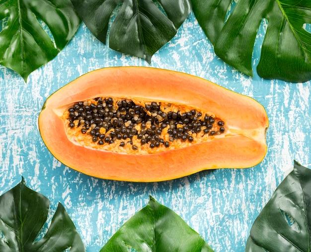 Papayafrucht des halben schnittes mit monsterablättern Kostenlose Fotos