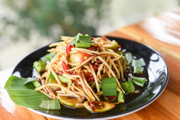 Papayasalat auf esstisch würziges thailändisches lebensmittel des grünen papayasalats Premium Fotos