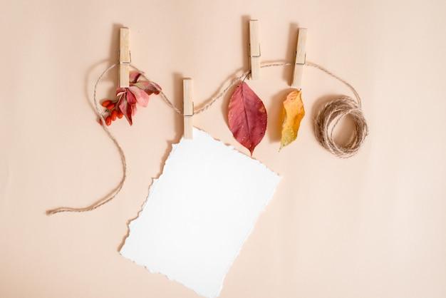 Papier für ihre notizen. zerrissenes papier trend.autumn blätter in einer wäscheleine von wäscheklammern gehalten. holunderbeere und berberitze, früchte und trockene blätter. herbstkarte, flache lage, draufsicht. copyspace. Premium Fotos