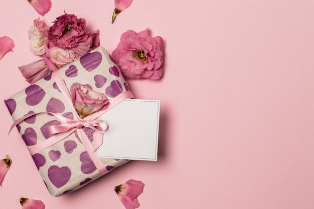 Papier in der nähe von geschenk und blumen und blütenblätter Kostenlose Fotos