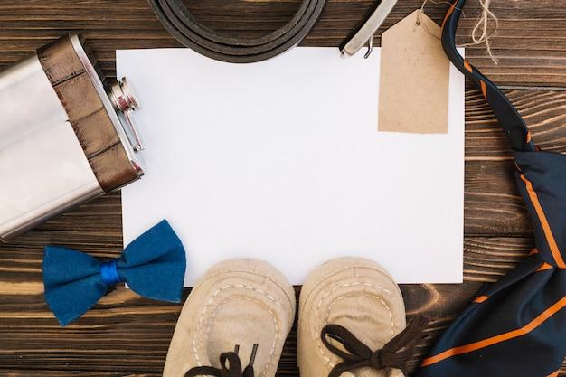 Papier in der nähe von männlichen accessoires und kinderschuhen Kostenlose Fotos