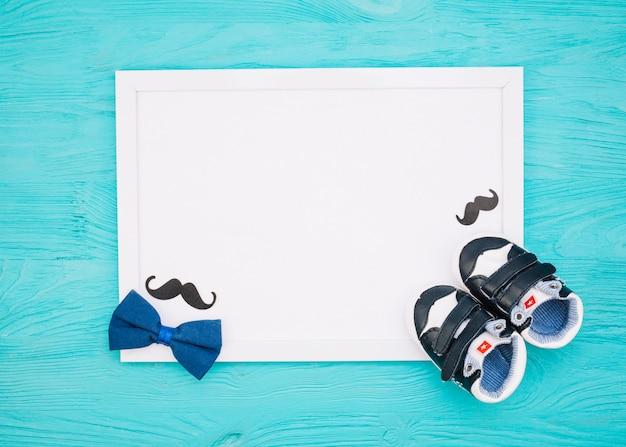 Papier in der nähe von schnurrbart, fliege und kinderschuhen Kostenlose Fotos