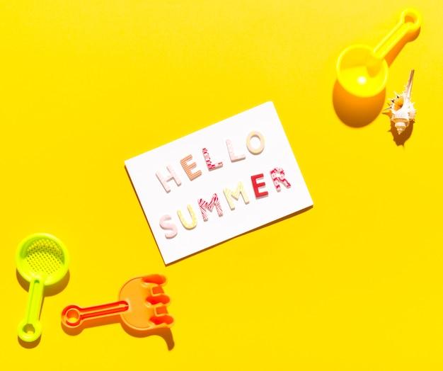 Papier mit der aufschrift hallo sommer und schaufeln für sandkästen Kostenlose Fotos