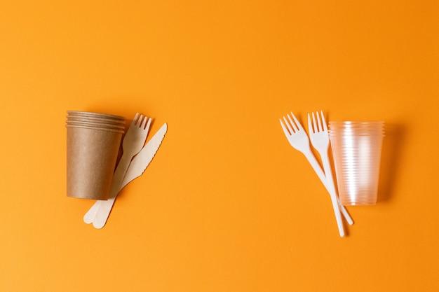 Papier- und plastikschalen auf einem orangefarbenen hintergrund. konfrontationskonzept. naturschutz. probleme der ökologie, des recyclings und der rettung der natur. Premium Fotos
