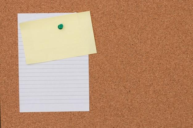 Papieranmerkung mit druckbolzen auf korkenbretthintergrund. Premium Fotos