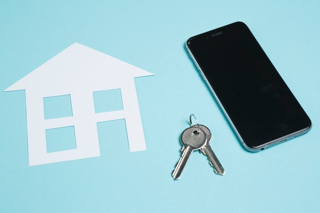 Papierausschnitt des hauses und der schlüssel mit mobiltelefon auf blauem hintergrund Kostenlose Fotos