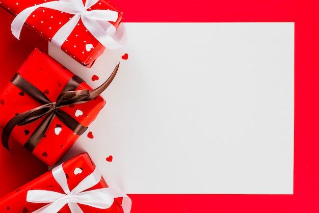 Papierblatt in der nähe von geschenken zum valentinstag Kostenlose Fotos
