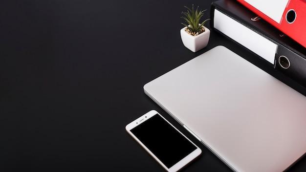 Papierdateien; topfpflanze; geschlossener laptop und smartphone auf schwarzem hintergrund Kostenlose Fotos