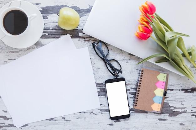 Papiere und kaffeetasse nahe smartphone auf schreibtisch mit tulpe blüht Kostenlose Fotos