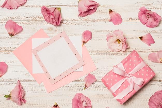 Papiere zwischen blumen in der nähe der geschenkbox Kostenlose Fotos