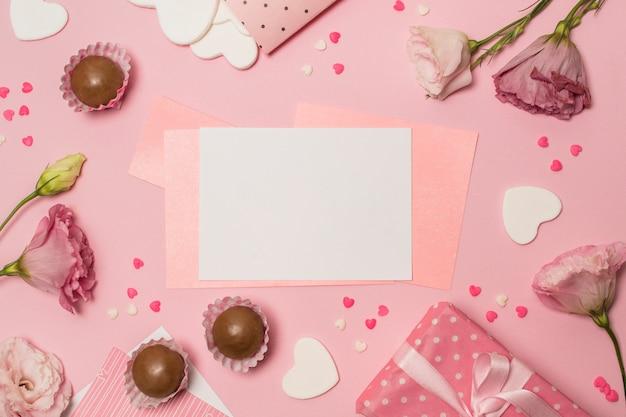 Papiere zwischen blumen in der nähe von geschenkschachtel und pralinen Kostenlose Fotos