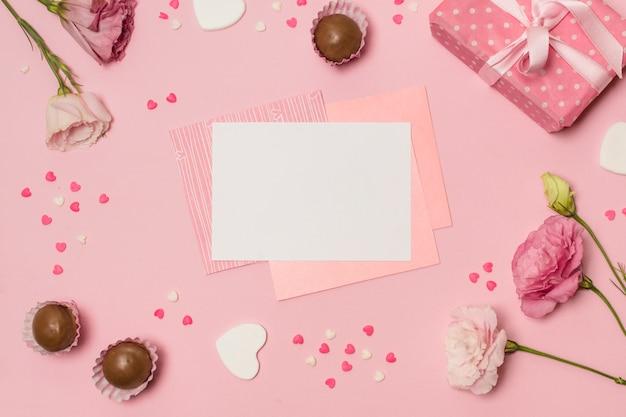 Papiere zwischen symbolen von herzen, süßigkeiten, geschenk und blumen Kostenlose Fotos