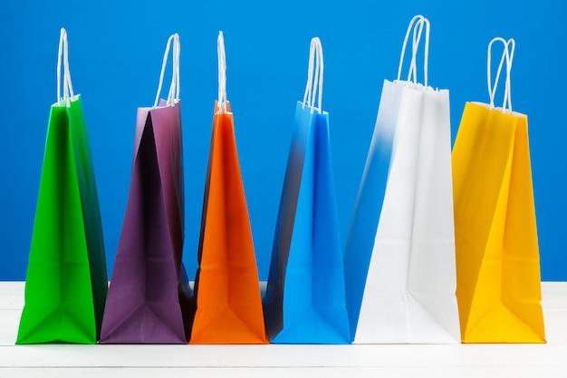 Papiereinkaufstaschen mit kopienraum auf blauem hintergrund Premium Fotos